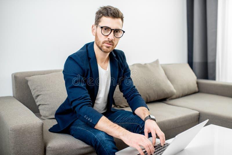 Hombre de negocios que trabaja con el ordenador portátil en casa foto de archivo