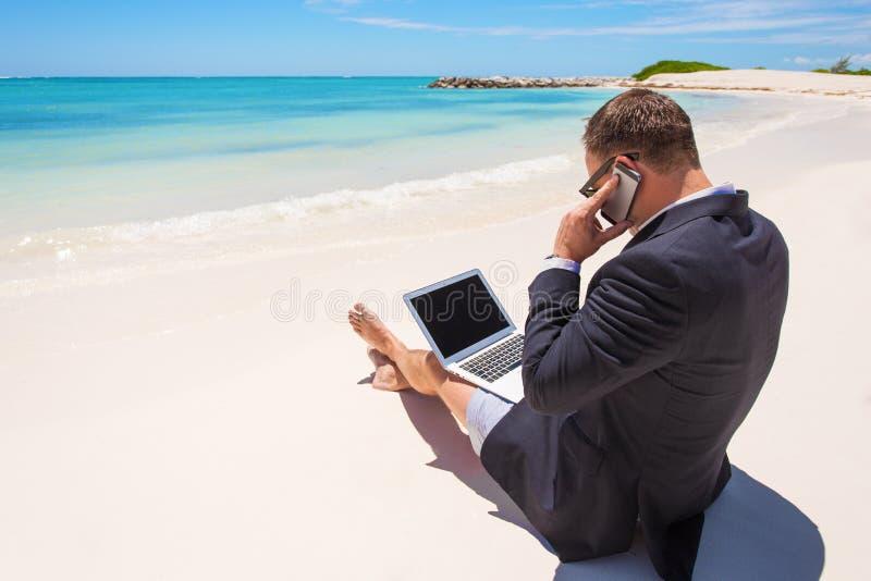 Hombre de negocios que trabaja con el ordenador y que habla en el teléfono en la playa imagen de archivo