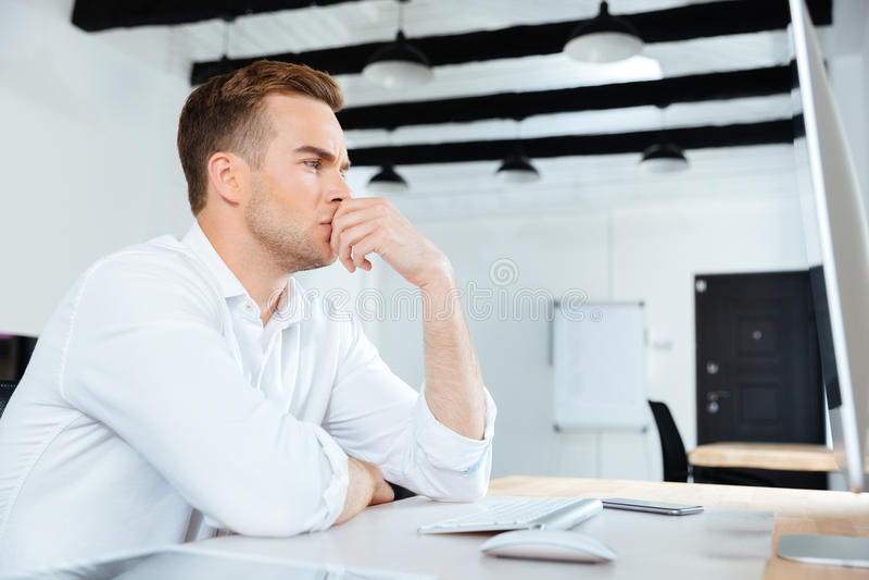 Hombre de negocios que trabaja con el ordenador y que piensa en el lugar de trabajo imagenes de archivo