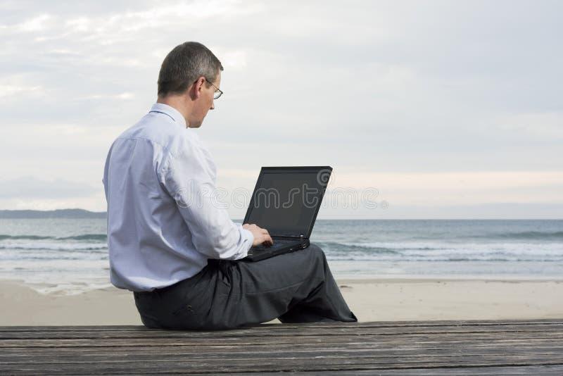 Hombre de negocios que trabaja con la computadora portátil en una playa fotos de archivo
