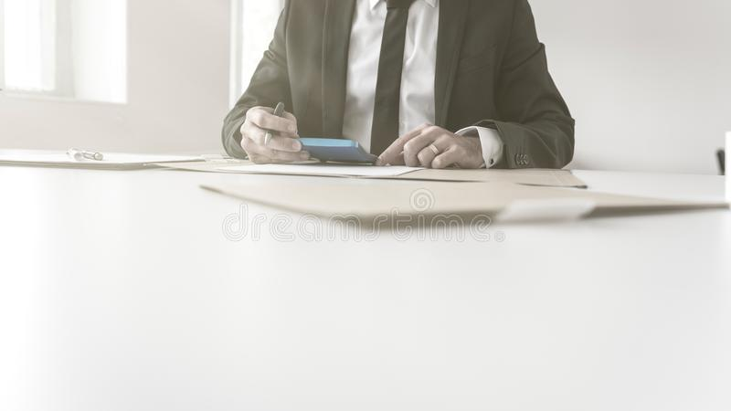 Hombre de negocios que trabaja en el equilibrio de sus libros imagen de archivo libre de regalías
