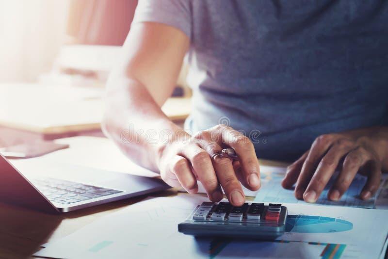 hombre de negocios que trabaja en el escritorio usando la calculadora para calcular datos de las finanzas imagen de archivo