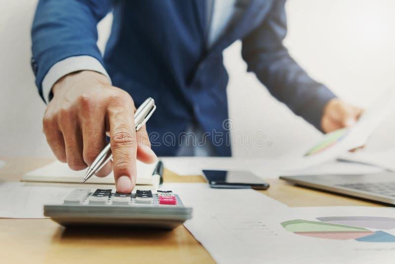 hombre de negocios que trabaja en el escritorio y que usa la calculadora fotografía de archivo