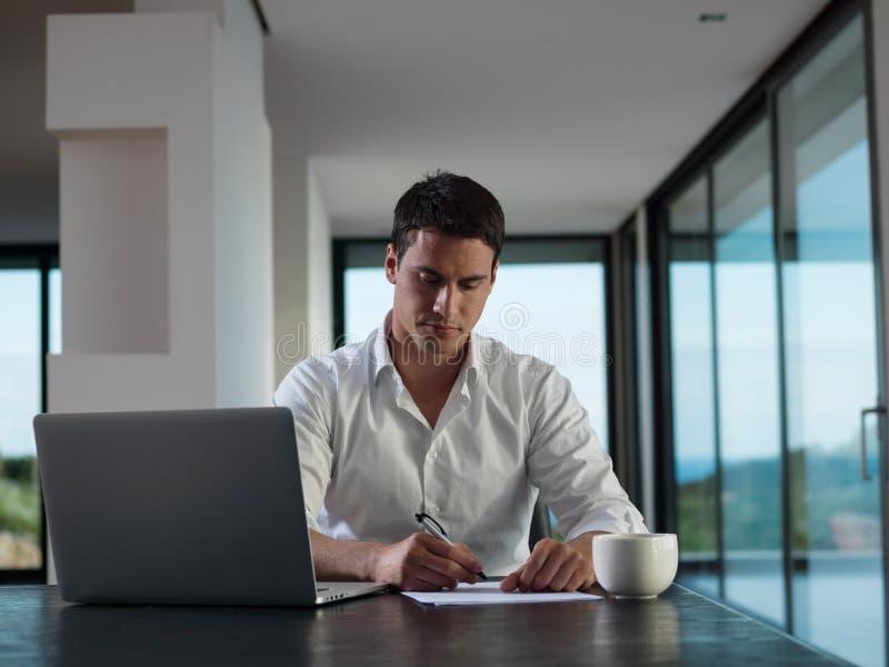 Hombre de negocios que trabaja en el ordenador portátil en casa fotografía de archivo libre de regalías