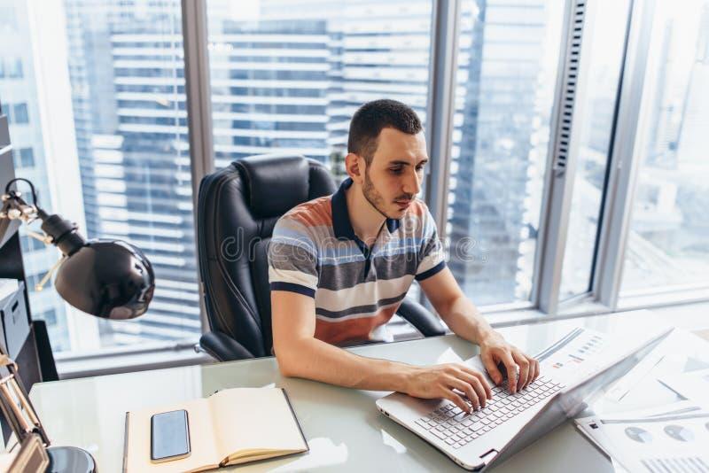 Hombre de negocios que trabaja en el ordenador portátil usando Internet que busca para la información que se sienta en el escrito foto de archivo libre de regalías