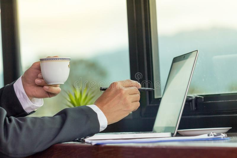 Hombre de negocios que trabaja en el ordenador portátil y el café de consumición fotografía de archivo