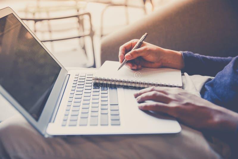 Hombre de negocios que trabaja en el ordenador portátil y que escribe el cuaderno imagenes de archivo