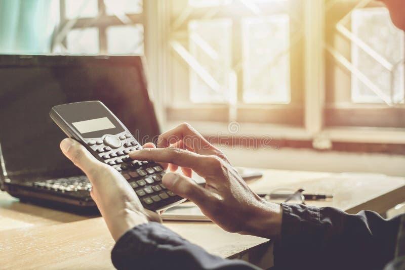 Hombre de negocios que trabaja en la calculadora y el ordenador con el fondo del concepto del negocio de la puesta del sol imagenes de archivo