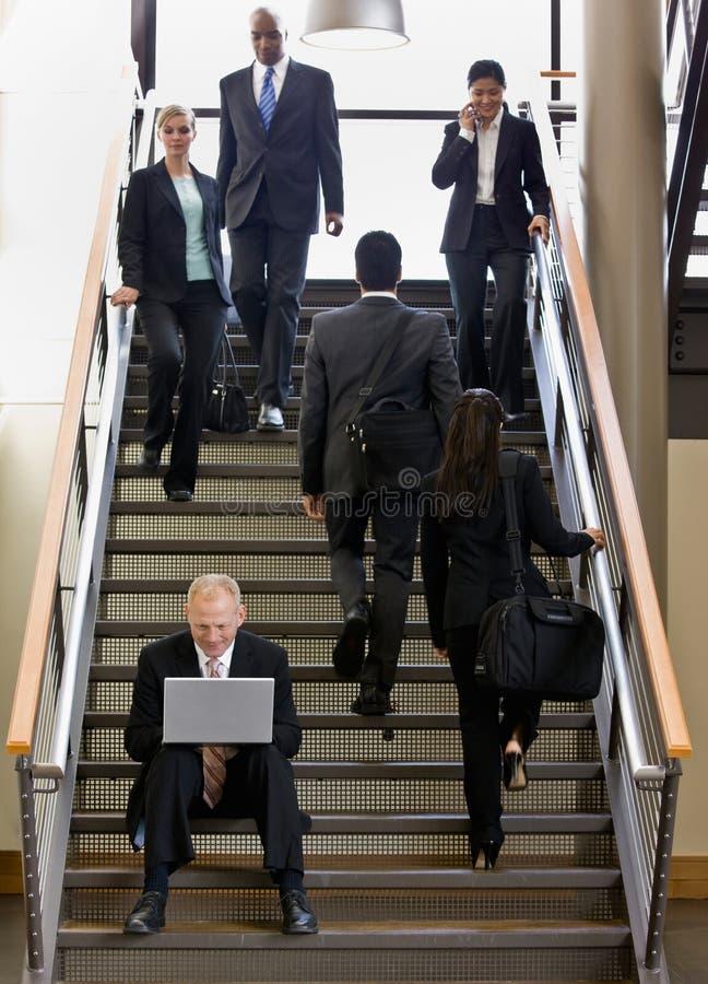 Hombre de negocios que trabaja en la computadora portátil en las escaleras de la oficina imagen de archivo libre de regalías