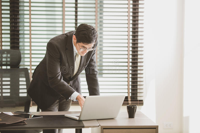 Hombre de negocios que trabaja en la oficina con el ordenador portátil en su escritorio fotos de archivo