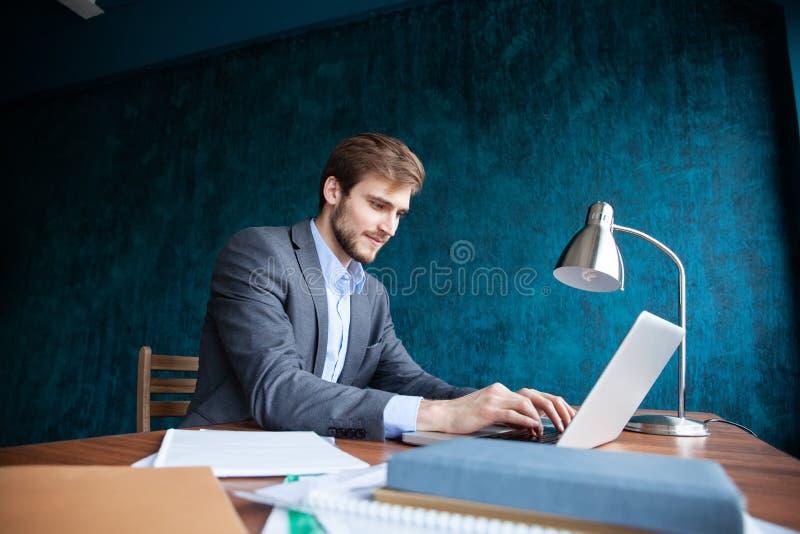 Hombre de negocios que trabaja en la oficina con el ordenador portátil y los documentos en su escritorio, concepto del abogado de imagen de archivo libre de regalías