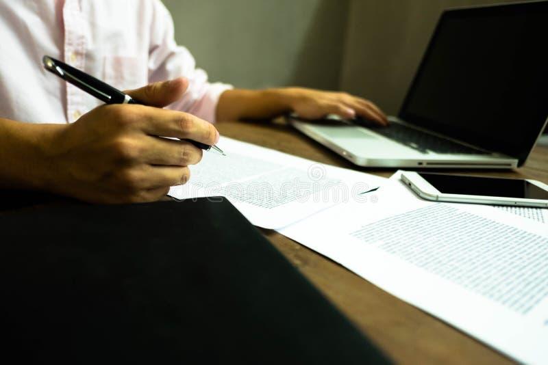Hombre de negocios que trabaja en la oficina con el ordenador portátil y los documentos en el t imagenes de archivo