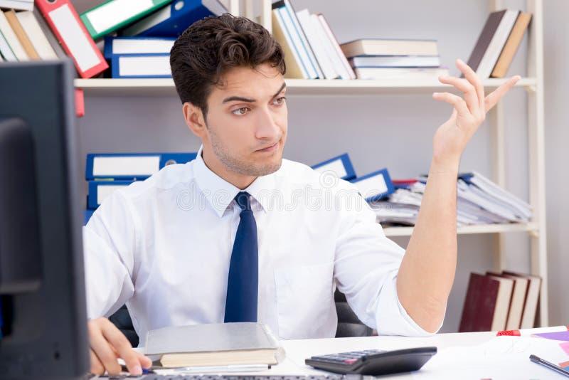 Hombre de negocios que trabaja en la oficina con las pilas de libros y de papeles imagen de archivo libre de regalías