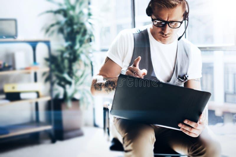 Hombre de negocios que trabaja en la oficina moderna en su tableta digital que se sostiene en manos Hombre atractivo que lleva la fotos de archivo