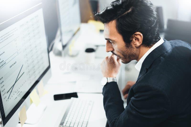Hombre de negocios que trabaja en la oficina soleada en el equipo de escritorio mientras que se sienta en la tabla Fondo borroso, fotografía de archivo libre de regalías