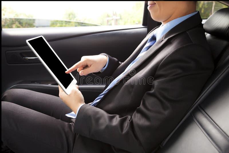 Hombre de negocios que trabaja en la parte de atrás del coche y que usa una tableta fotos de archivo