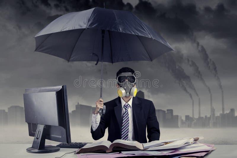 Hombre de negocios que trabaja en la situación de la contaminación atmosférica fotografía de archivo libre de regalías