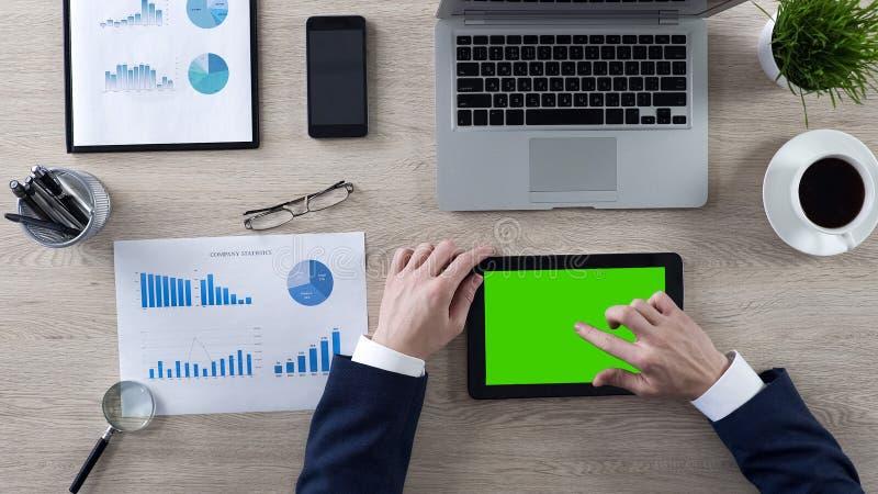 Hombre de negocios que trabaja en la tableta con la pantalla verde, vista superior del lugar de trabajo fotografía de archivo libre de regalías