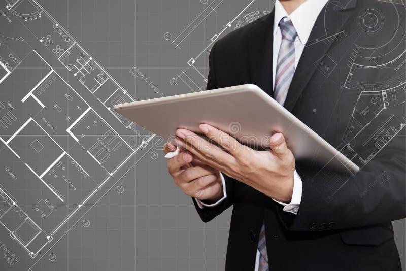 Hombre de negocios que trabaja en la tableta digital con el fondo arquitectónico del dibujo del plan del modelo, arquitecto, conc imagen de archivo libre de regalías