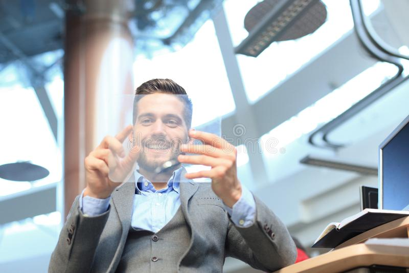 Hombre de negocios que trabaja en oficina con el ordenador transparente de la tableta y de la PC imágenes de archivo libres de regalías