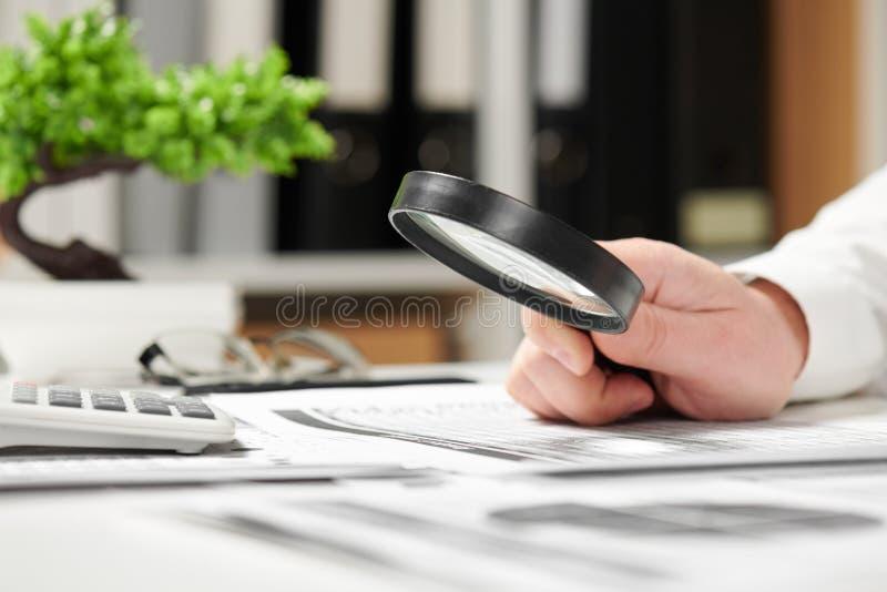 Hombre de negocios que trabaja en oficina y que calcula finanzas Usando la lupa concepto de la contabilidad financiera del negoci fotos de archivo