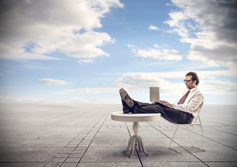 Hombre de negocios que trabaja en su ordenador portátil fotografía de archivo