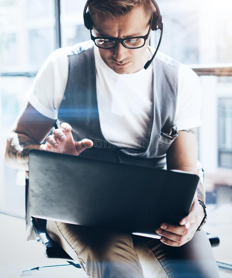 Hombre de negocios que trabaja en su tableta digital que se sostiene en manos Hombre elegante que lleva las auriculares audios y  fotografía de archivo libre de regalías