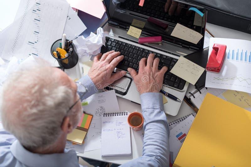 Hombre de negocios que trabaja en un escritorio estorbado y sucio fotografía de archivo