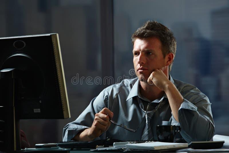 Hombre de negocios que trabaja tarde en oficina imagen de archivo