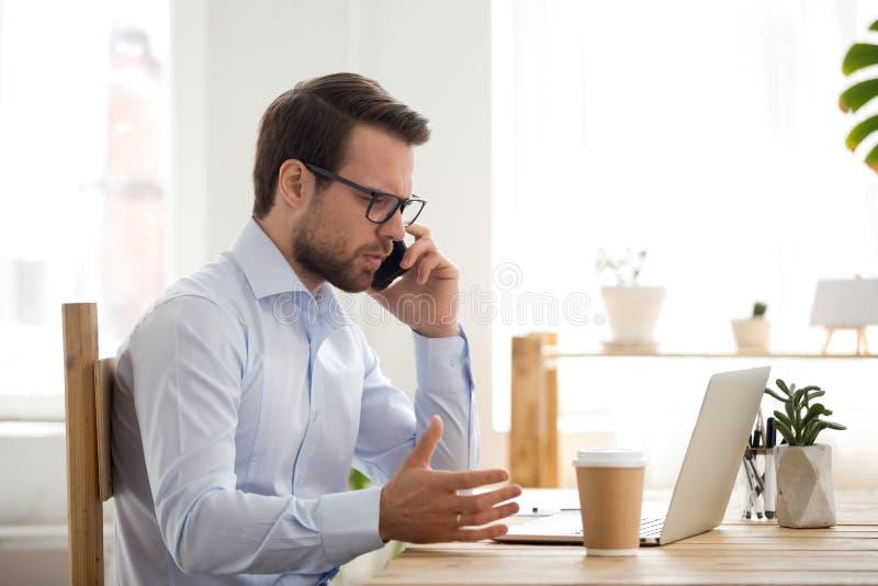 Hombre de negocios que trabaja usando smartphone y el ordenador en oficina fotos de archivo