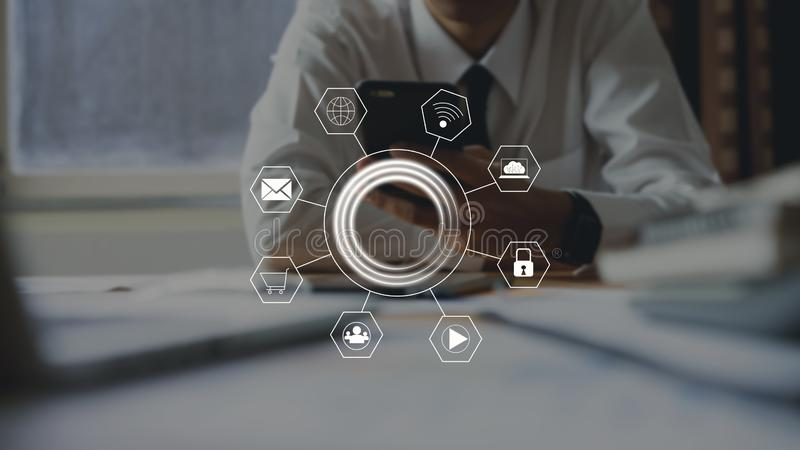 Hombre de negocios que usa el icono de la tecnología de la muestra del smartphone y de la demostración foto de archivo libre de regalías