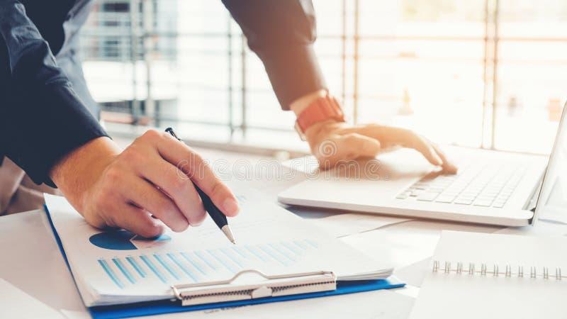 Hombre de negocios que usa el ordenador portátil con la carta del informe en la oficina que planea n fotografía de archivo libre de regalías