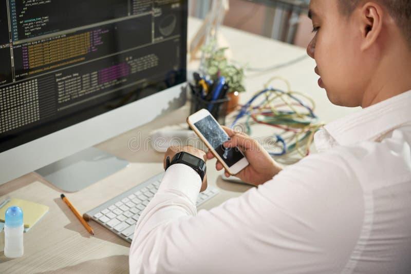 Hombre de negocios que usa el smartwatch para contestar en llamada imagenes de archivo