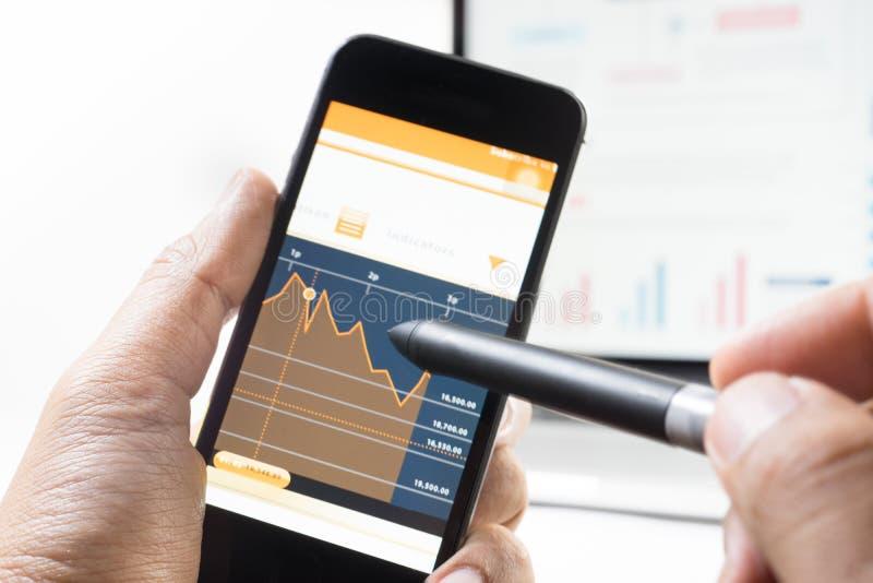 Hombre de negocios que usa la pluma con un dispositivo y un gráfico del teléfono móvil fotos de archivo libres de regalías