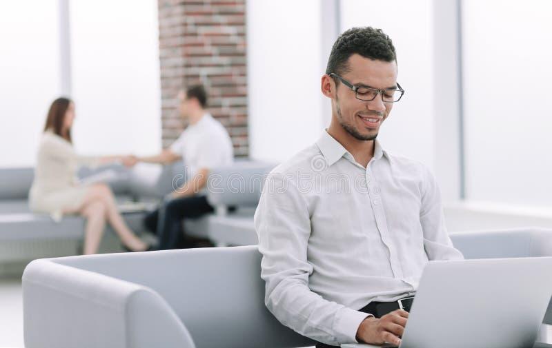 Hombre de negocios que usa su ordenador portátil mientras que se sienta en el pasillo de la oficina imágenes de archivo libres de regalías