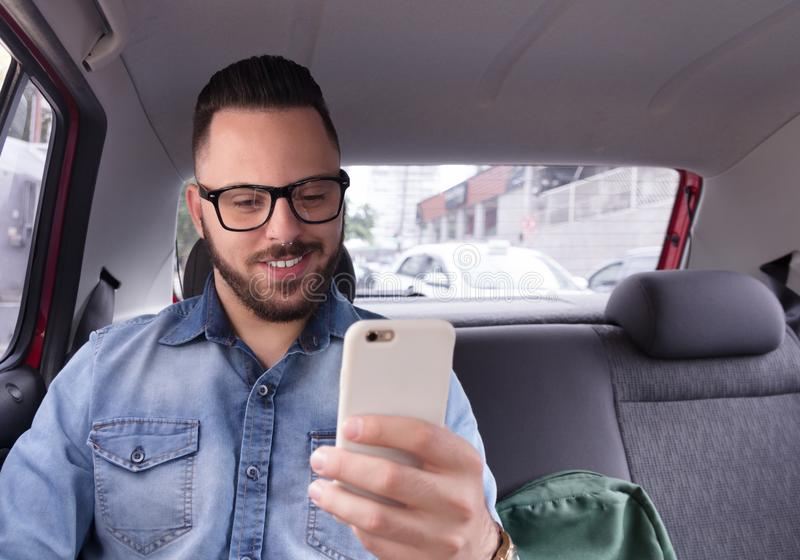 Hombre de negocios que usa su teléfono elegante mientras que en su conmute para trabajar en privado el transporte del vehículo Co fotos de archivo