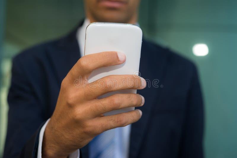 Hombre de negocios que usa su teléfono móvil foto de archivo libre de regalías