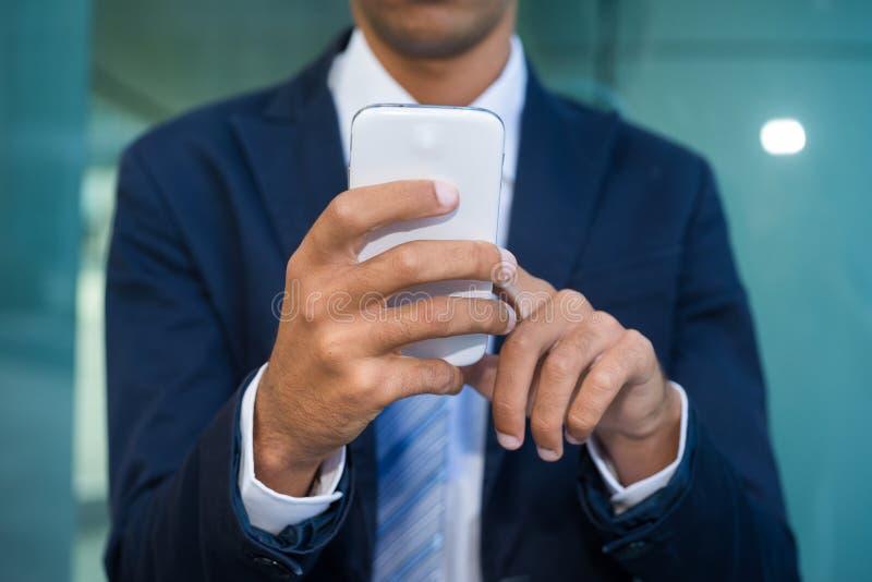 Hombre de negocios que usa su teléfono móvil foto de archivo