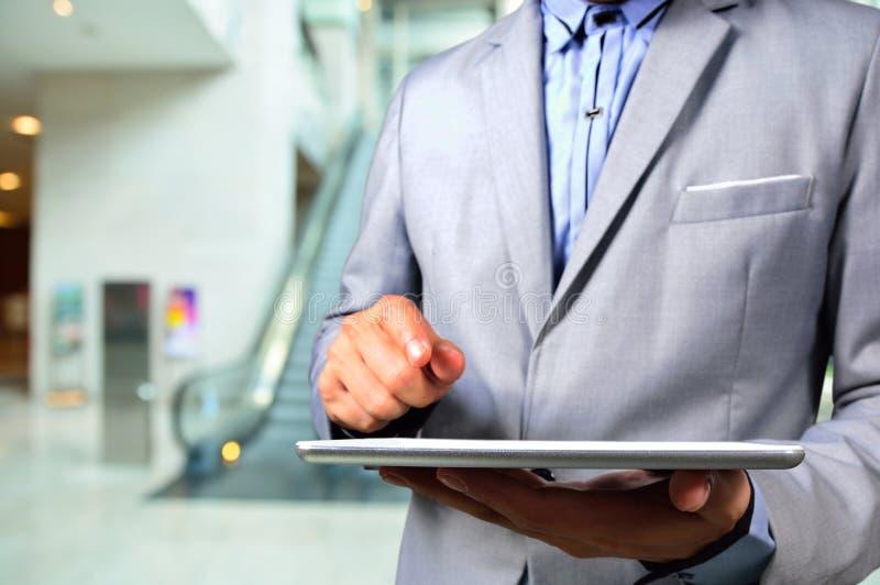 Hombre de negocios que usa Tablet PC en escalera móvil del edificio de oficinas fotos de archivo libres de regalías