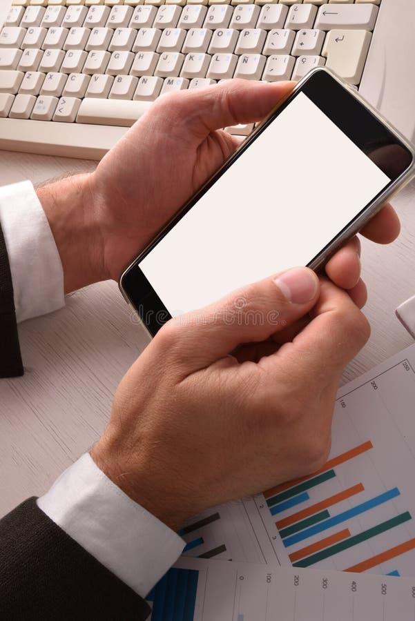 Hombre de negocios que usa un smartphone en la vertical de la opinión superior de la oficina foto de archivo