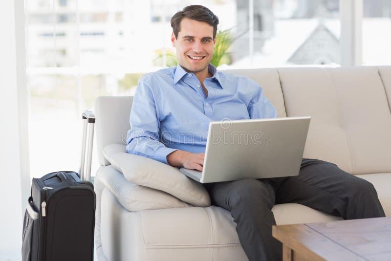 Hombre de negocios que viaja usando el ordenador portátil que se sienta en el sofá que sonríe en la cámara fotos de archivo libres de regalías