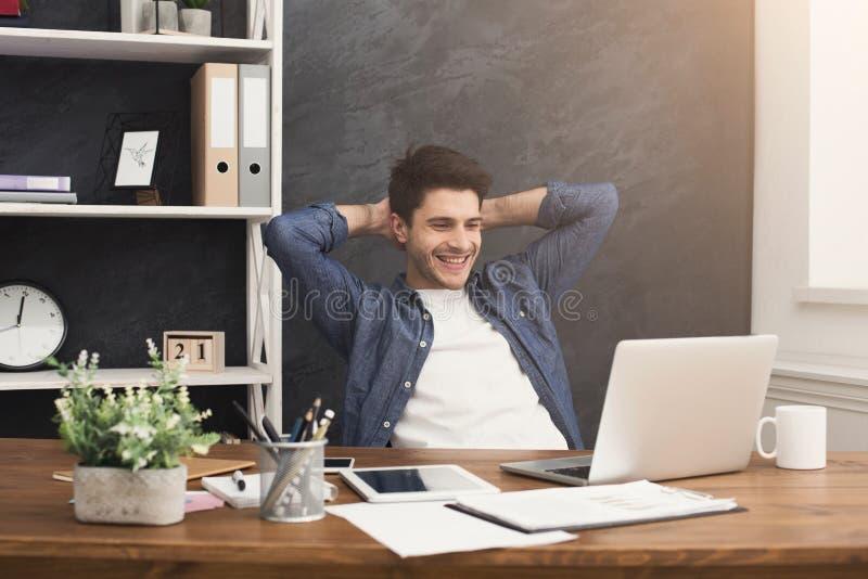 Hombre de negocios relajado joven con el ordenador portátil en oficina imagen de archivo