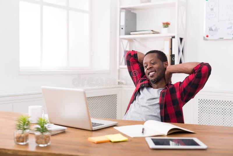 Hombre de negocios relajado joven con el ordenador portátil en oficina blanca moderna fotografía de archivo