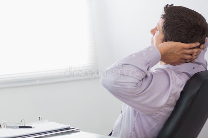 Hombre de negocios relajado pensativo que se sienta en oficina fotografía de archivo