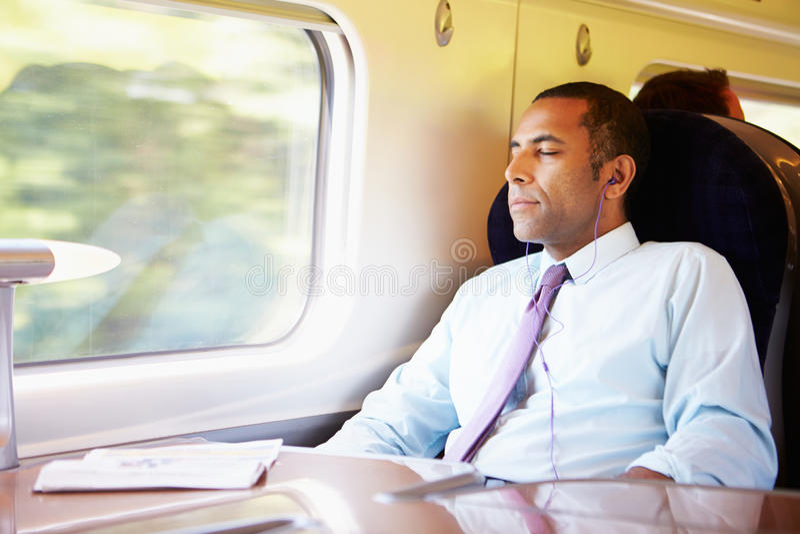 Hombre de negocios Relaxing On Train que escucha la música imagen de archivo