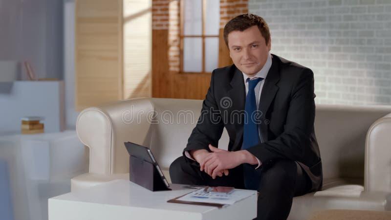 Hombre de negocios respetable que se sienta en el sofá en la oficina moderna, carrera acertada fotografía de archivo libre de regalías