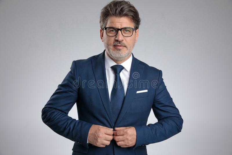 Hombre de negocios resuelto que ajusta su chaqueta foto de archivo