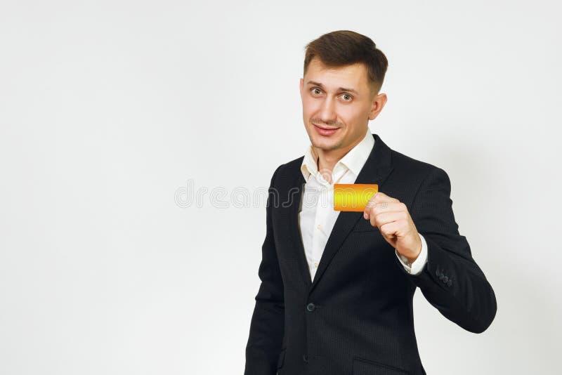 Hombre de negocios rico hermoso acertado joven en traje negro en el fondo blanco para hacer publicidad foto de archivo libre de regalías