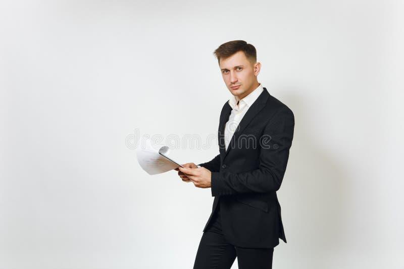 Hombre de negocios rico hermoso acertado joven en traje negro en el fondo blanco para hacer publicidad imagen de archivo libre de regalías