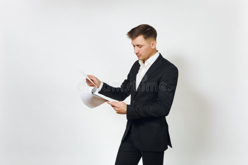 Hombre de negocios rico hermoso acertado joven en traje negro en el fondo blanco para hacer publicidad fotografía de archivo